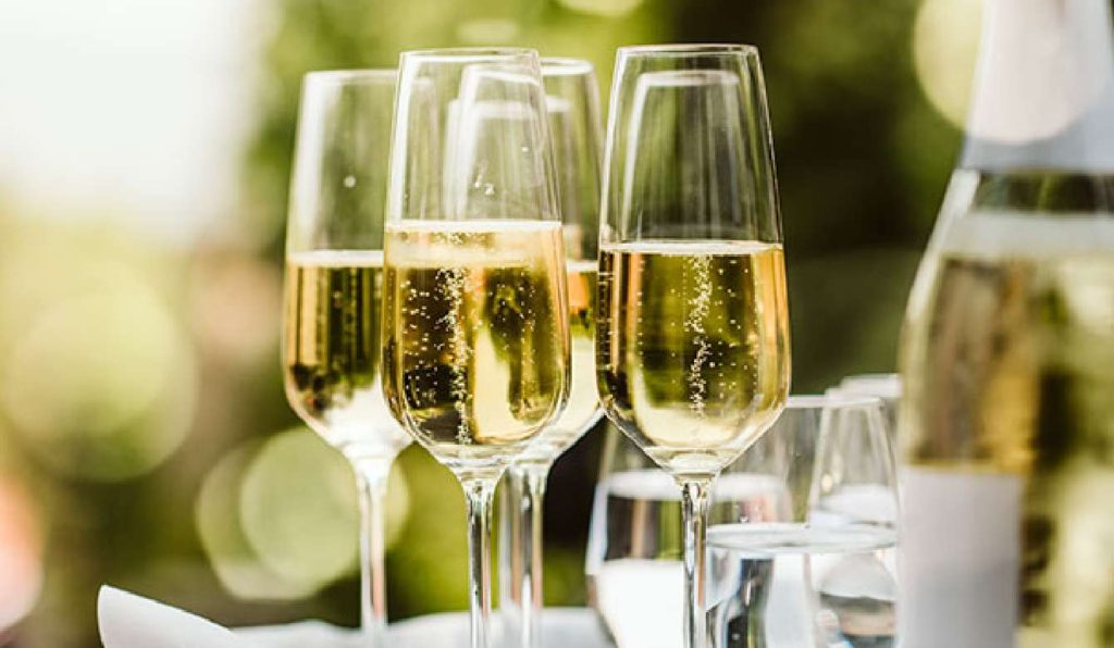 Multiple glasses of prosecco waiting to be served at an event