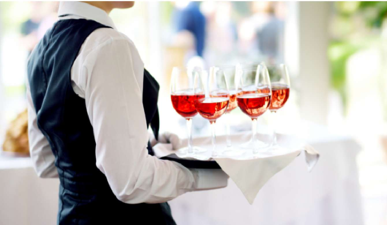 Waiter holding five glasses of rose wine