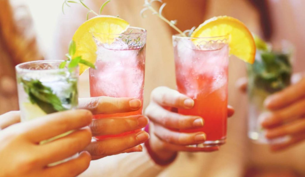 Four people holding red and green cocktails